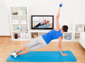 Young Woman Exercising in Front of TV